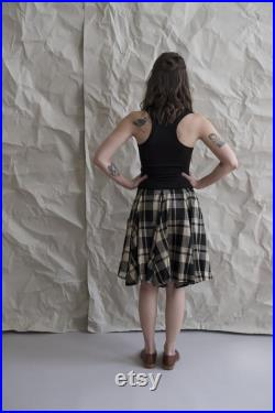 Black and tan plaid circle skirt. Two generous side pockets and a tall stretchy waistband for function and comfort. Fit and flare, easy fit.